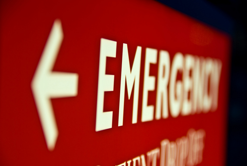Red emergency sign indicating the direction to the hospital